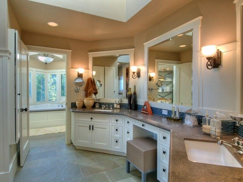 This primary bathroom offers two sinks with beautiful countertop lighted by wall lights. The bathtub and the shower have its own room.