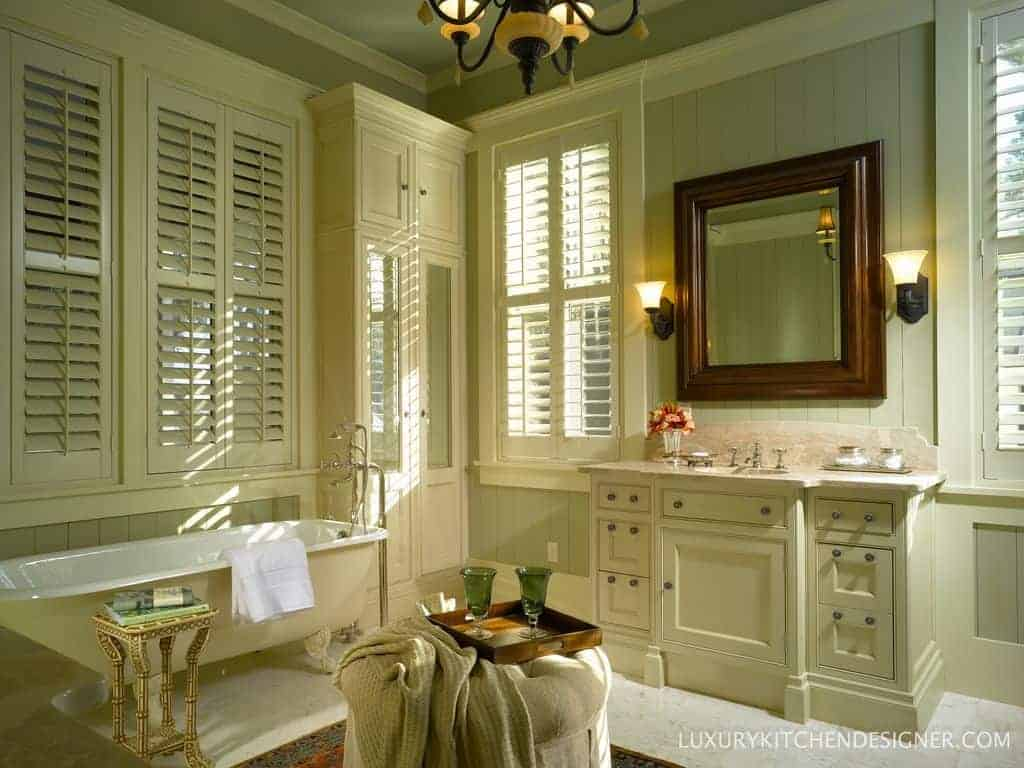 The warm bathroom offers a freestanding tub and a single vanity sink paired with a wooden mirror. It has sage green walls fixed with windows covered in white shutters.