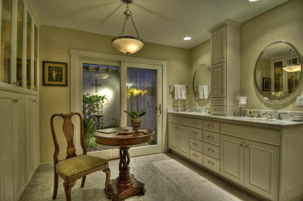 This primary bathroom offers a center table with a chair lighted by a pendant light. The sinks with marble countertop look very classy as well.