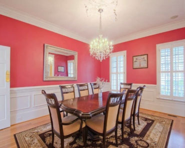 A rectangle dining table with chandelier and pink wall