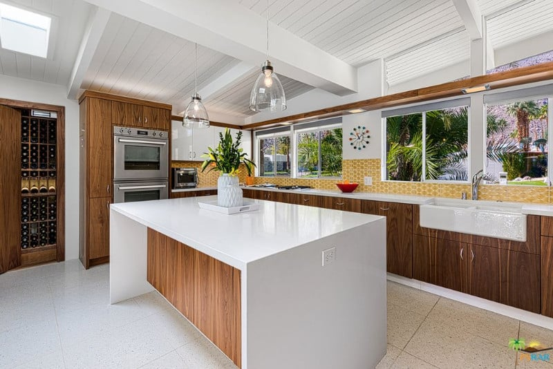 This kitchen offers a large white waterfall-style center island lighted by classy pendant lights set on the ceiling with beams.