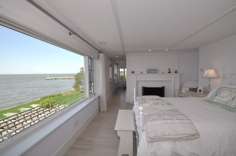 Clean white guest bedroom with light wood plank flooring and panoramic window overlooking a stunning ocean view. It includes a fireplace and comfy bed with a bench on its end.