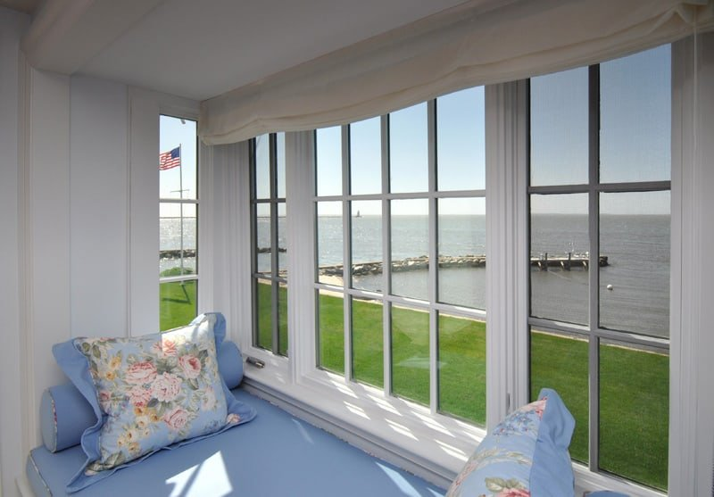 The property's sunroom with blue sofa bed and customized white glass windows, perfect for relaxation.
