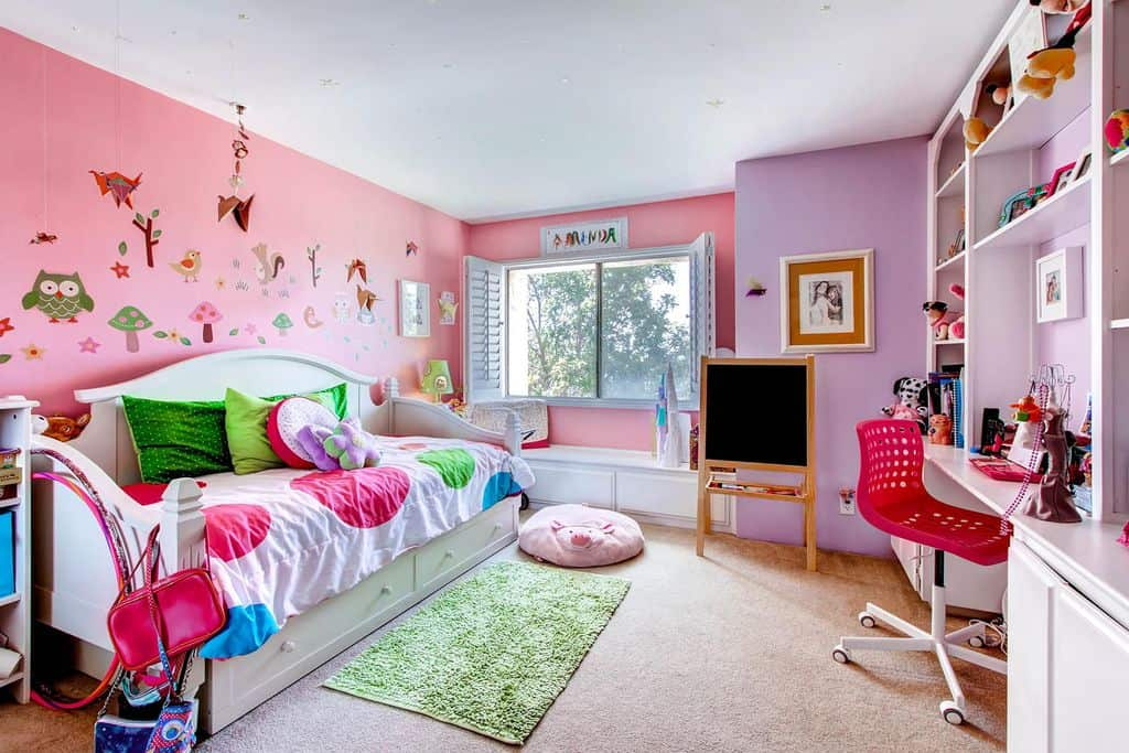 This girl's bedroom boasts pink and purple walls, along with carpet flooring and a rug. The study area looks perfect with the room's style.