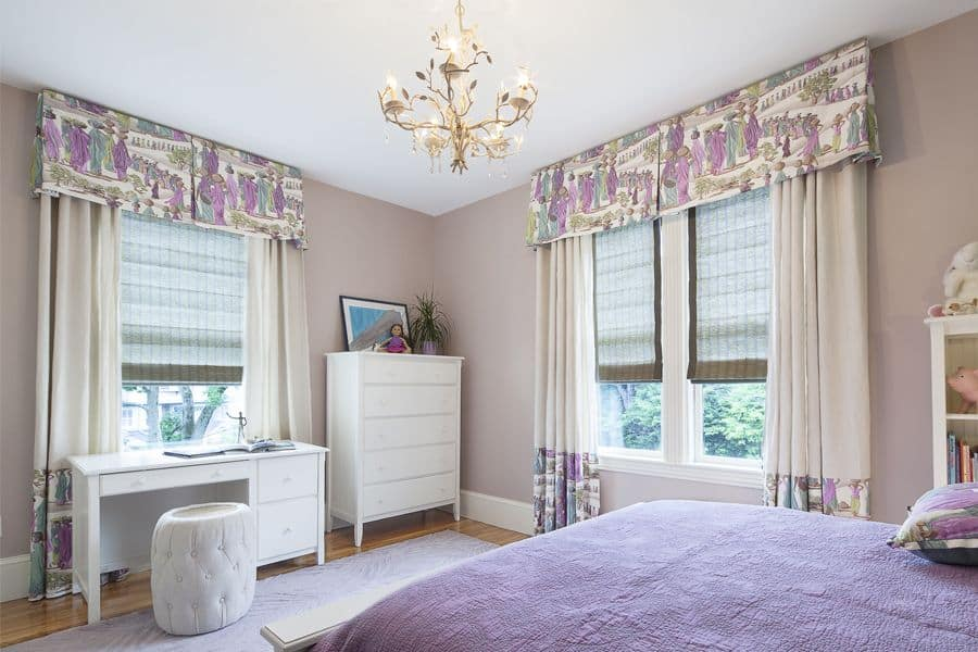 This girl's bedroom offers a large bed and a small desk lighted by a glamorous chandelier. The purple accent looks stylish as well.