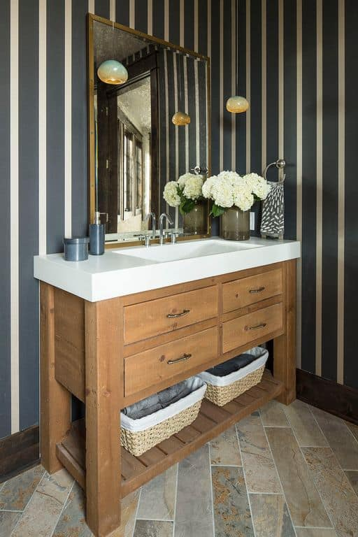 This powder room features tiled flooring and gray striped wallpaper. It has a wooden vanity with built-in shelf and drawers topped with a porcelain sink.