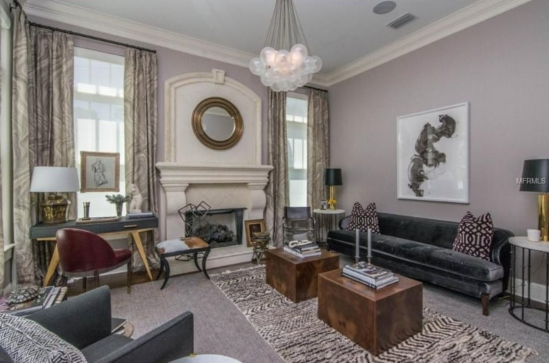 Formal living room showcases a classy fireplace and gray seats that are paired with cube coffee tables illuminated by a frosted bubble chandelier.