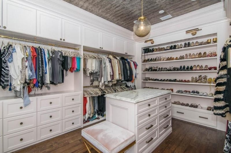 A walk-in closet with an island on the center.