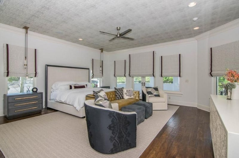 Large master bedroom featuring a sofa set on top of a rug covering the hardwood flooring.