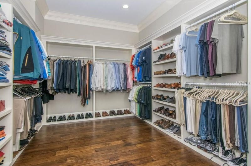 This bedroom closet features white walls and ceiling along with the cabinetry set on a hardwood flooring.