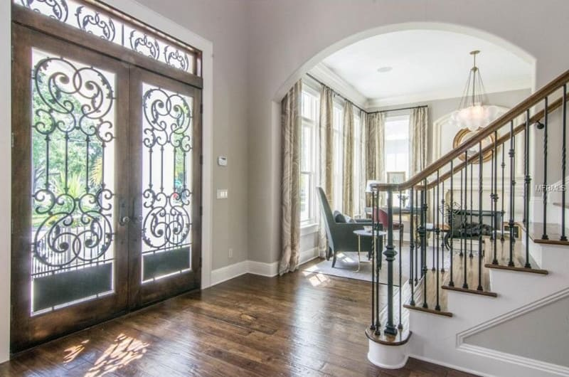 This classy foyer features a hardwood flooring, gray walls and an elegant door leading straight to the staircase.