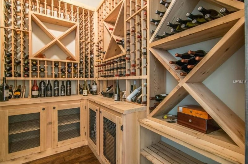 A close-up look of an L-shaped light wood wine cellar accented with X wine racks on a white wall.