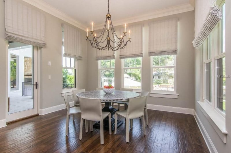 Gray dining room surrounded with glazed windows covered with roman shades. It has a round dining table and white chairs over wood plank flooring.