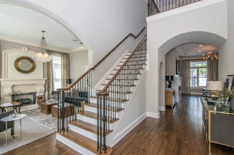 Foyer with a white staircase accented with wooden treads along with ornate wrought iron spindles topped with wooden handrail.