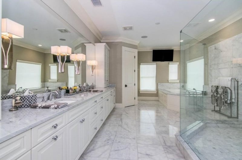 Large primary bathroom with marble tiles flooring and countertops. The sinks are lighted by lovely wall lights. There's a bathtub and a shower room as well.