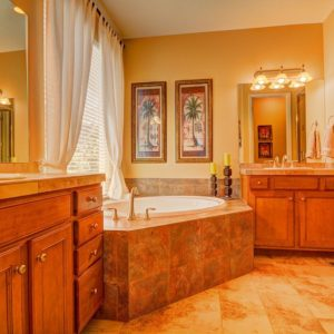 Craftsman orange primary bathroom with drop-in bathtub and tiles flooring.