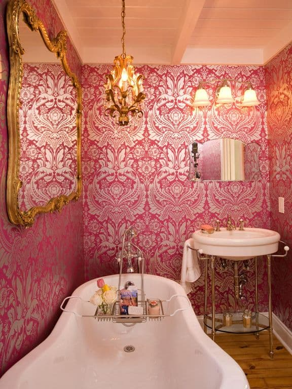 A huge gold mirror hangs above the bathtub in this primary bathroom clad in lovely pink wallpaper. There's a washstand on the side paired with a smaller mirror and sconces.