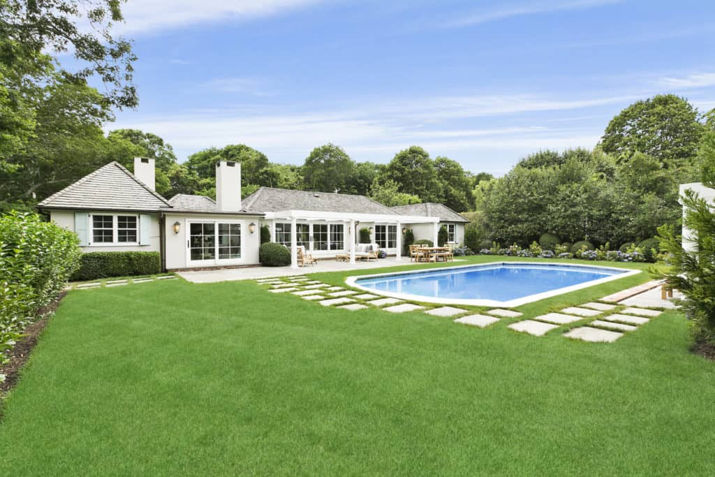 Rachael Ray's property's simple yet beautiful gunite pool with a patio in a separate white pool house.