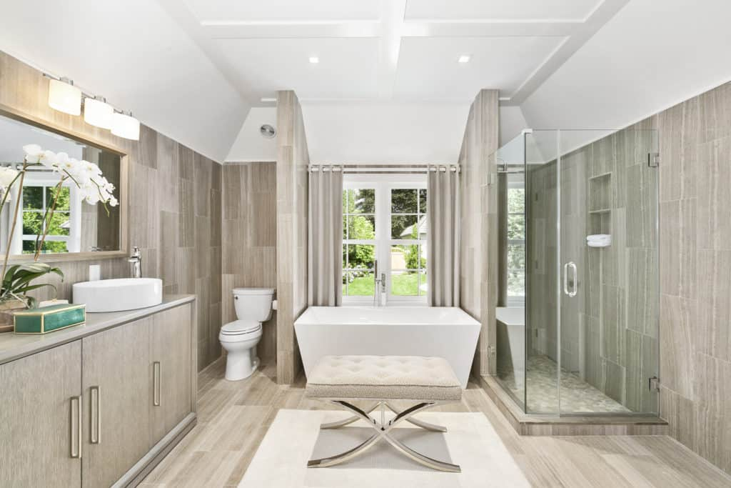 Large master bathroom with matching floors and walls along with a walk-in shower in the corner and a freestanding tub on the center.