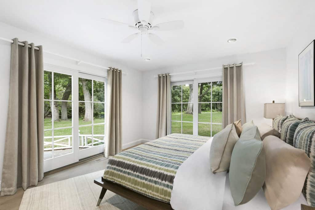 This master bedroom boasts white walls and ceiling. There's a doorway leading to the property's garden.