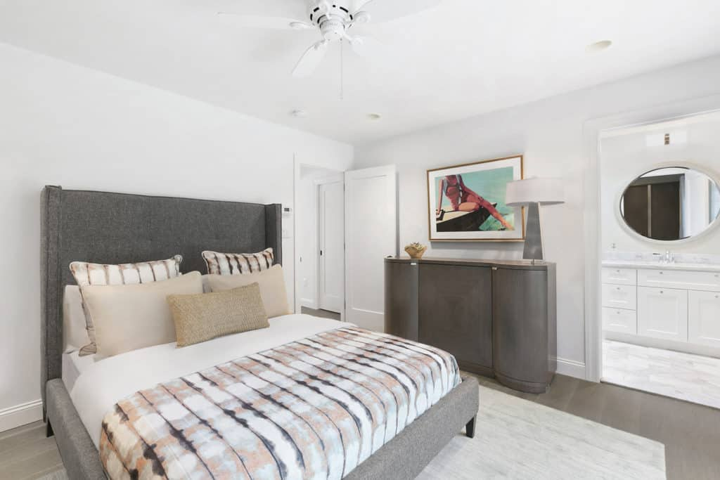 A framed wall art hangs above the wooden console table in this guest bedroom with modern table lamp and gray upholstered bed dressed in charming striped bedding.