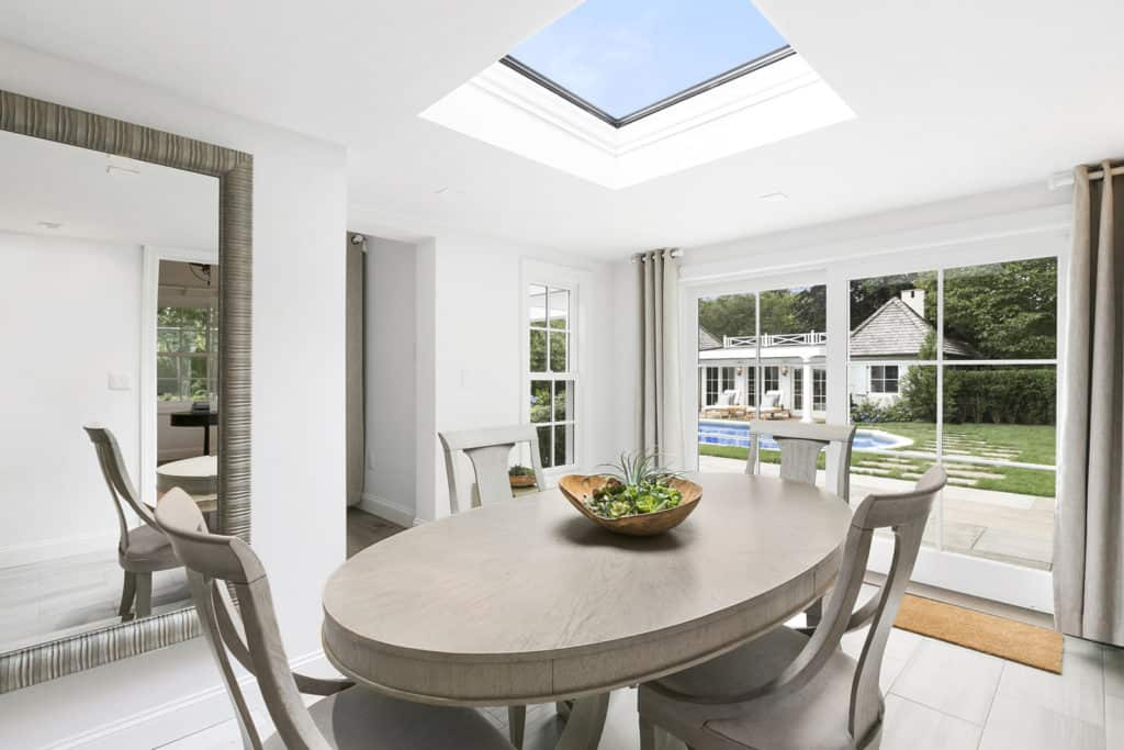 An oval dining table set paired with gray seats and is lighted by a skylight on a white ceiling matching the white walls surrounding the area.
