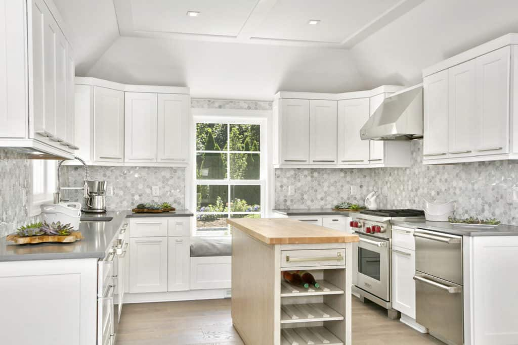 U-shaped kitchen with stylish backsplash and white cabinetry and counters.