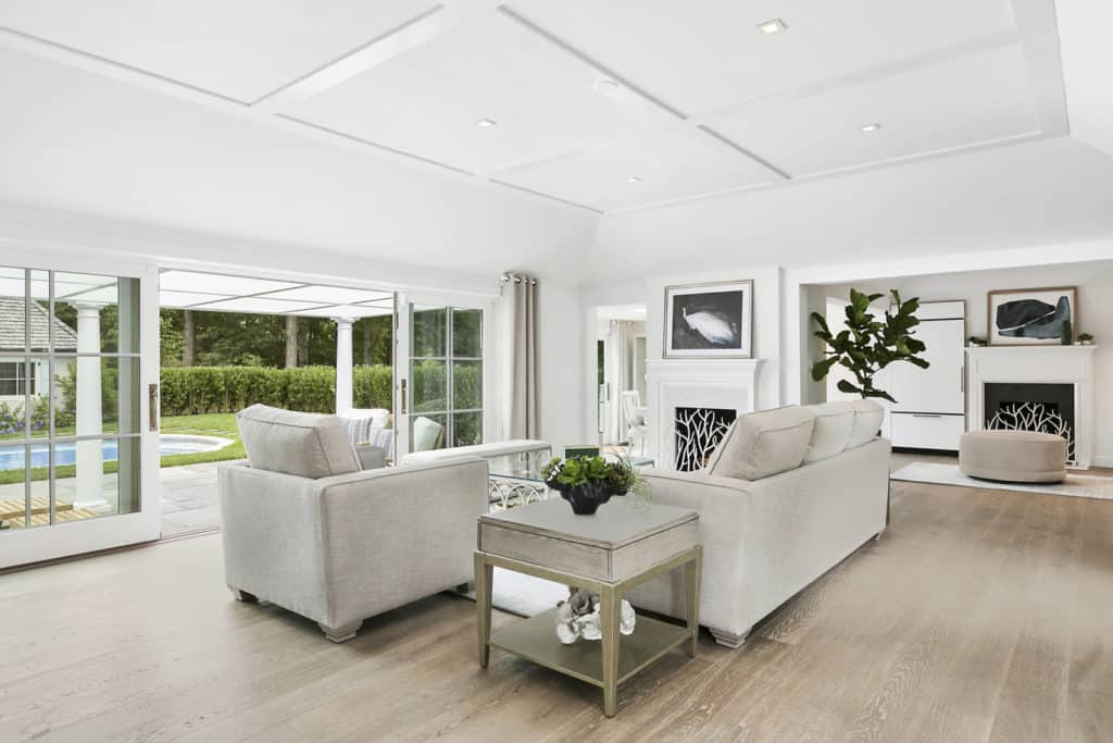 White living room with coffered ceiling and glass sliding doors that open to the lush green yard with a sparkling swimming pool. It includes a gray sofa set and fireplace covered in twig screen.