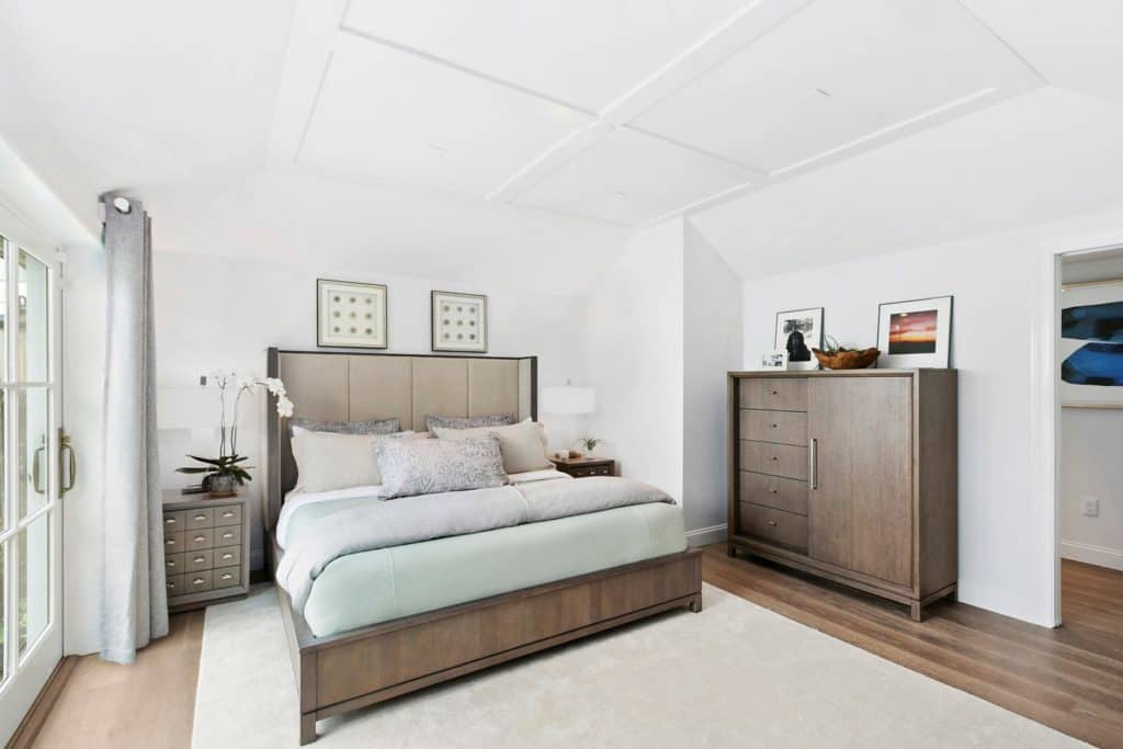 White guest bedroom filled with nightstands and a gorgeous wooden bed that complements with the dresser topped by lovely wall arts.
