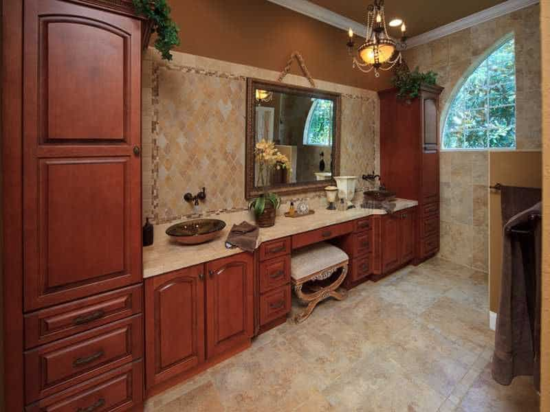 This primary bathroom showcases a long redwood vanity with dual vessel sinks, a beige stool and a framed mirror mounted on the diamond pattern backsplash. The ambient light from the warm chandelier provides a cozy atmosphere.