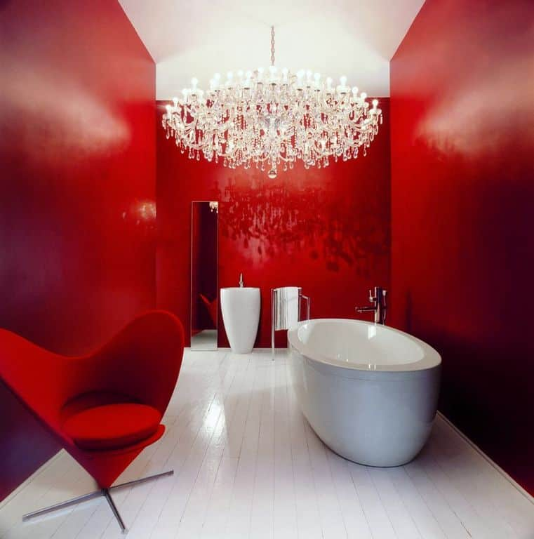 Vibrant red primary bathroom styled with an oversized crystal chandelier and a stylish heart-shaped chair that sits beside the freestanding tub over white wood plank flooring.