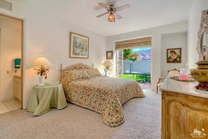This guest bedroom offers a wooden drawer and bed dressed in floral bedding. It matches with the roman shade wrapping the French door that leads out to the patio.