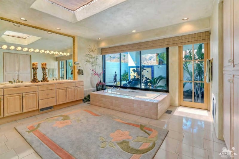 Spacious primary bathroom with a skylight and recessed ceiling lights. It also offers a soaking tub and a large rug set on the white tiles floors.