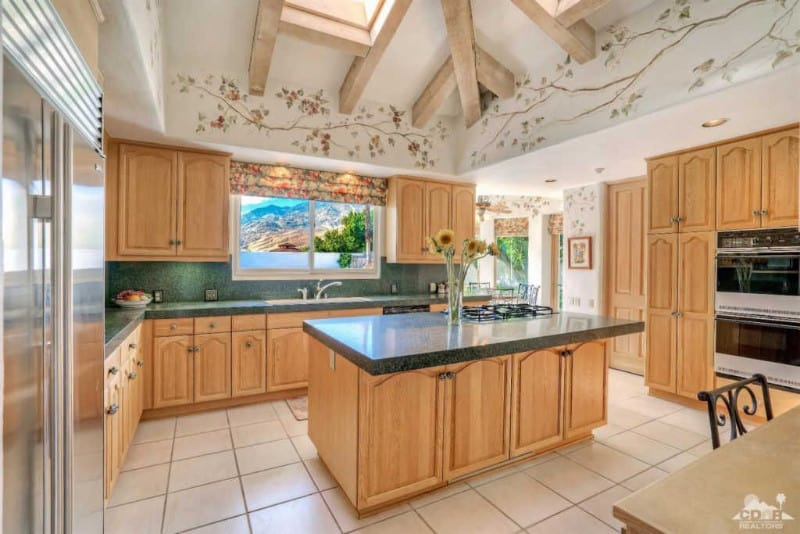 This kitchen boasts a ceiling with beams with added lovely design. The walnut finished cabinetry and kitchen counters with granite countertops look so classy as well.