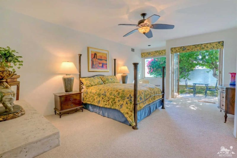 Airy guest bedroom accented with yellow floral curtains and bedding covering the four-poster bed on a carpet flooring.
