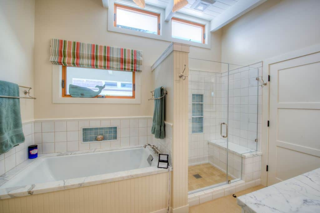 A close up look at this master bathroom's soaking tub and walk-in shower in the corner.