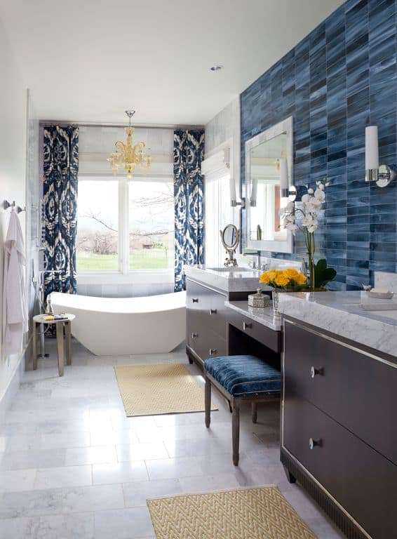 This primary bathroom features a tiles flooring and blue stylish walls. There's a freestanding tub on the corner near the window.