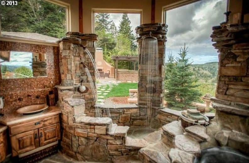 This luxurious bathroom boasts stunning open shower and bathtub made of large stones.