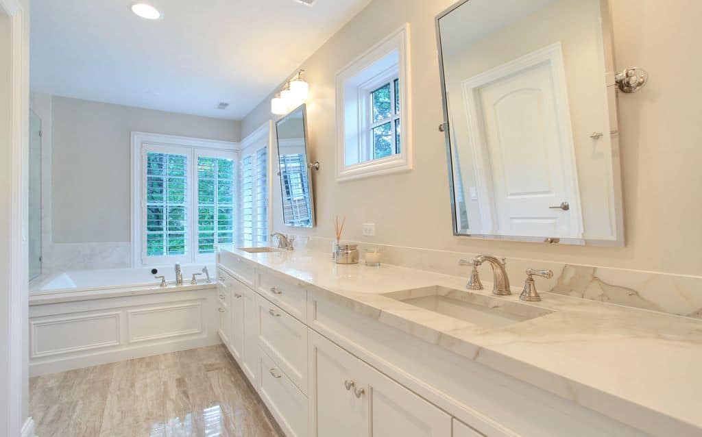 This large primary bathroom features white walls and white marble countertop with two sinks. There's a bathtub in the corner too.