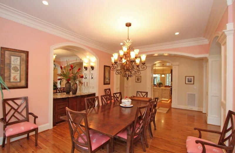 Traditional dining room features a wooden buffet table topped with a marble counter and frameless mirror fixed to the inset wall that's lighted by sconces. It has a dark wood dining table paired with pink cushioned chairs.