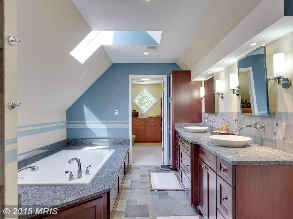 This primary bathroom offers a stunning deep soaking tub along with two vessel sinks set on the granite countertop.