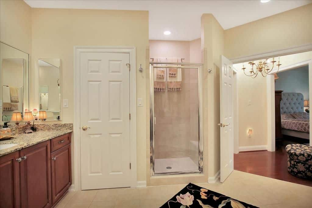 This master bathroom beside the master bedroom offers a shower room in the corner. The bathroom's counter offers granite countertop with a tiny lamp.