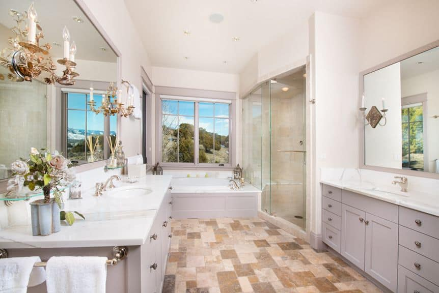Large primary bathroom with class tiles flooring and wall lights. The sinks also feature marble countertops. The bathtub is near the window and the walk-in shower is in the corner.
