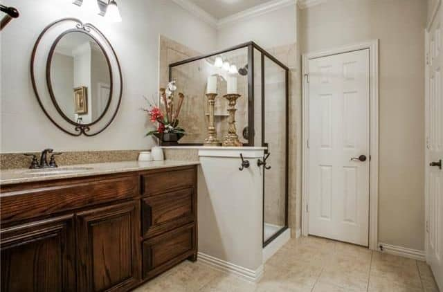 This master bathroom offers a classy walk-in shower in the corner. The lights look so classy together with the room's tiles flooring.
