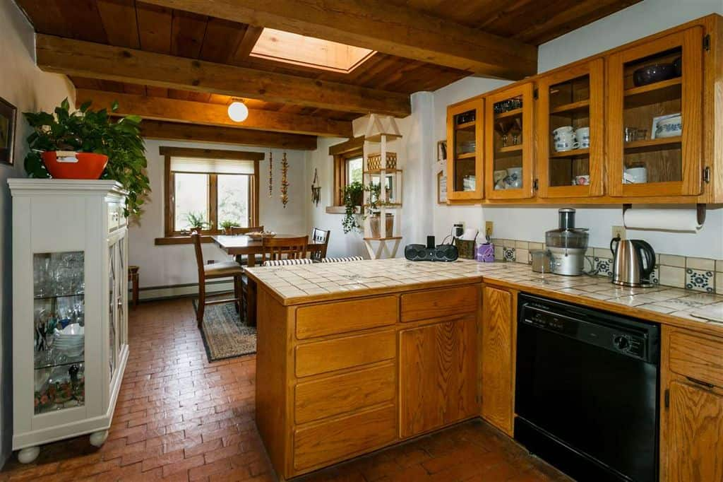 This kitchen features tiles countertop and brick tiles floors, along with a wooden ceiling with beams.