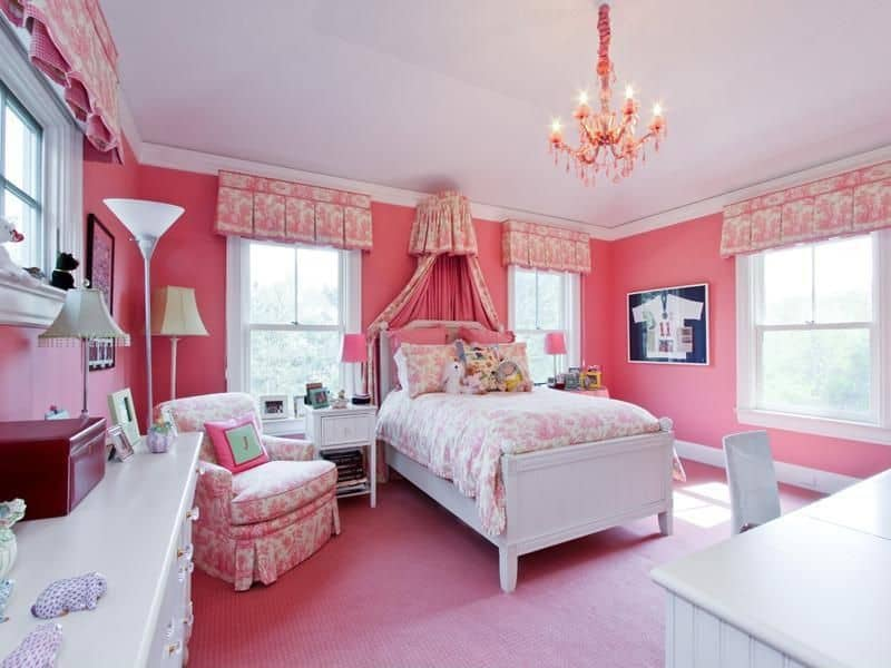 This girl's bedroom is surrounded by pink walls and floors, matching the lovely bed and seat. The room is lighted by a very charming chandelier.