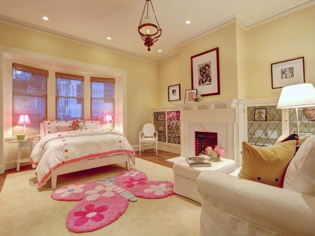 Large girl's bedroom with a fireplace on the side. the rugs look cute and lovely. The lights are very attractive as well.