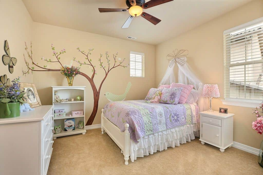 Small girl's bedroom featuring an interesting wall design on the beige walls matching the carpet flooring.