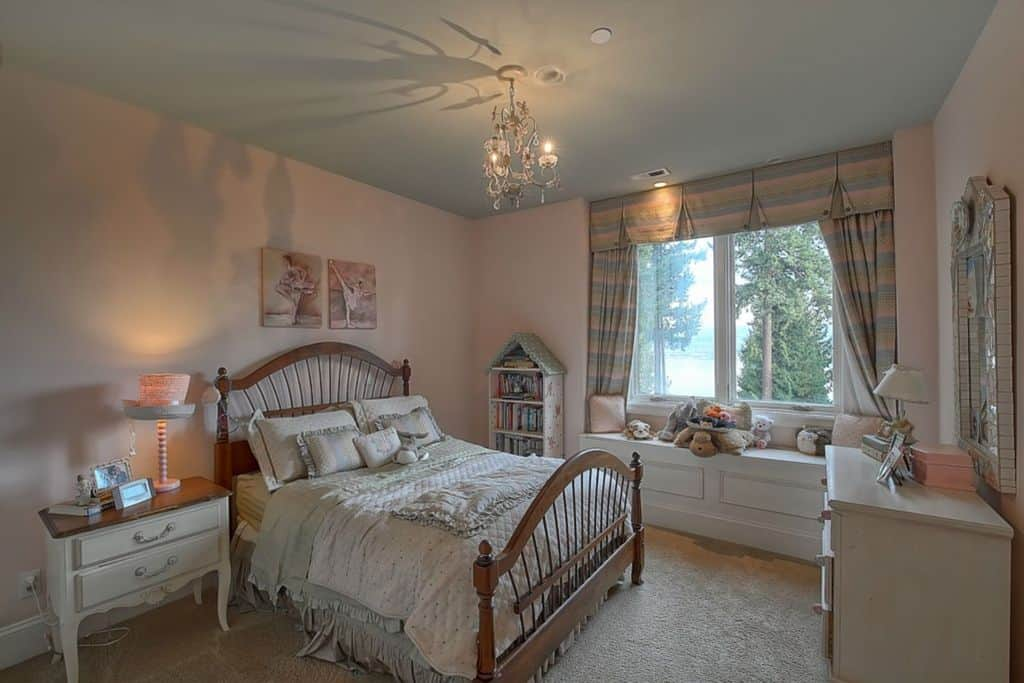 An elegant girl's bedroom with a carpet flooring and gray ceiling lighted by a small chandelier.