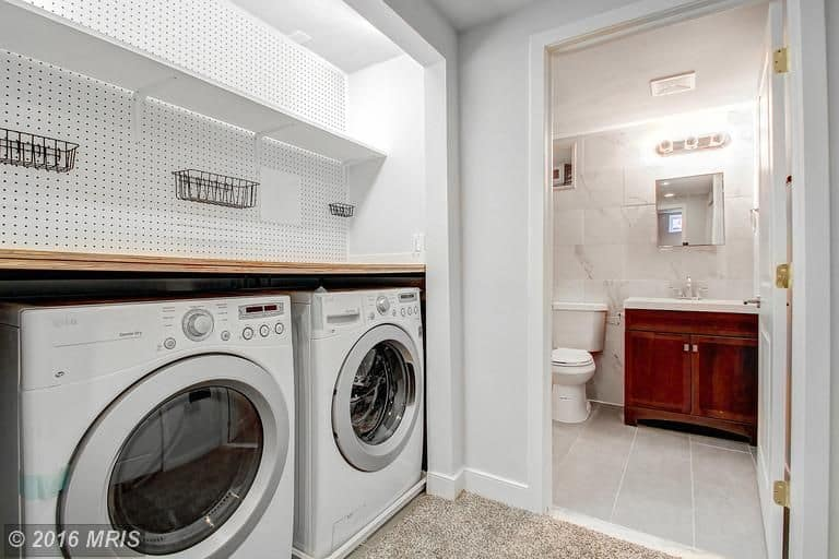A bathroom and laundry room combo featuring a stylish counter and white washer and dryer combo.
